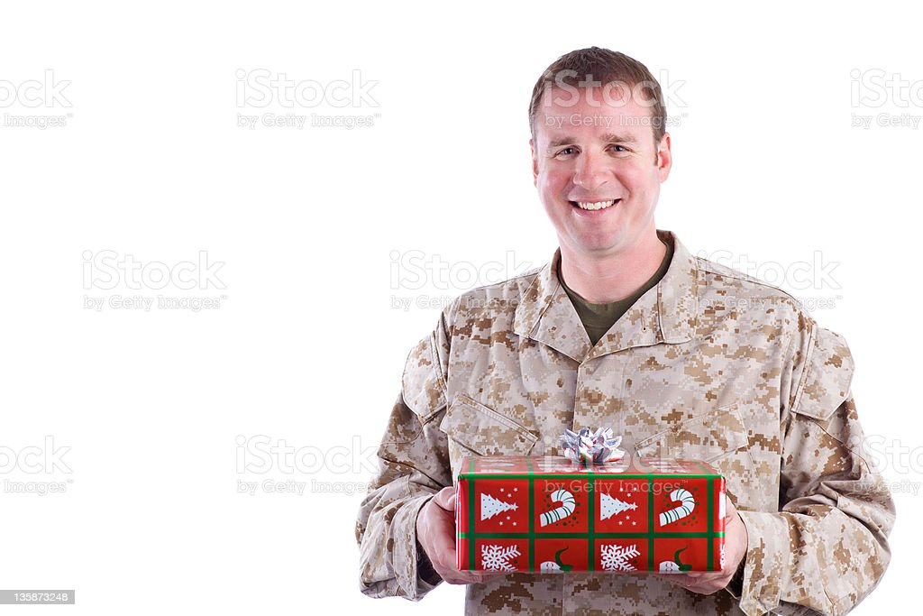 Military Man Holding a Christmas Present stock photo