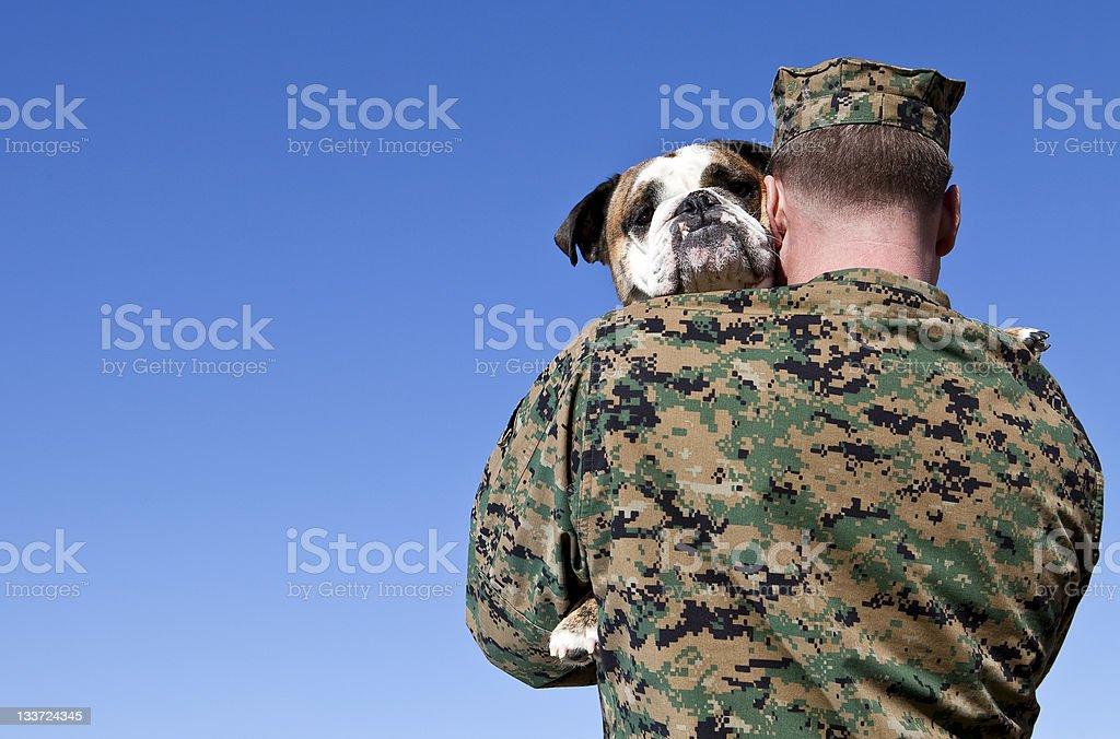 Military Man Hugs Dog stock photo