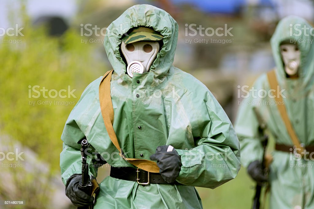 Military man in protective suit and gas mask outdoors. stock photo
