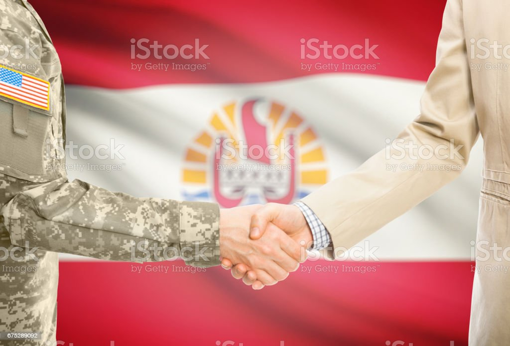 USA military man in uniform and civil man in suit shaking hands with national flag on background - French Polynesia stock photo