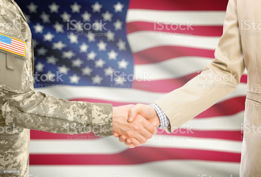 USA military man in uniform and civil man in suit shaking hands with national flag on background - United States stock photo