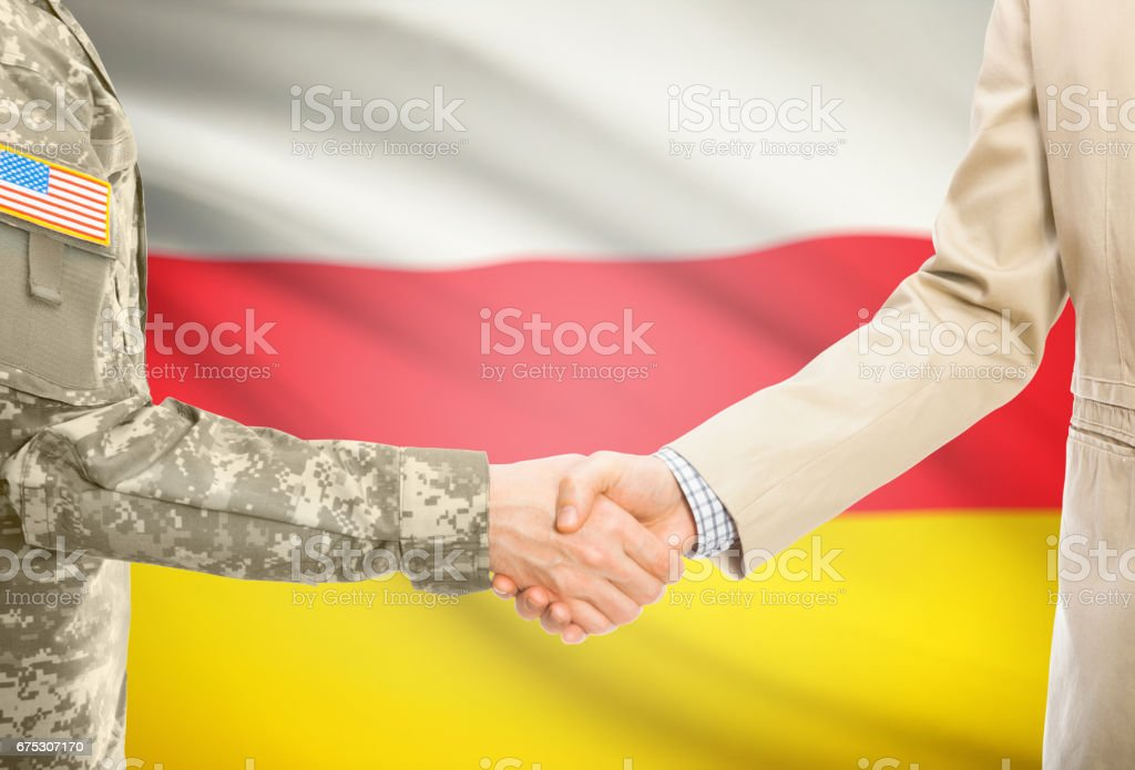 USA military man in uniform and civil man in suit shaking hands with national flag on background - South Ossetia stock photo
