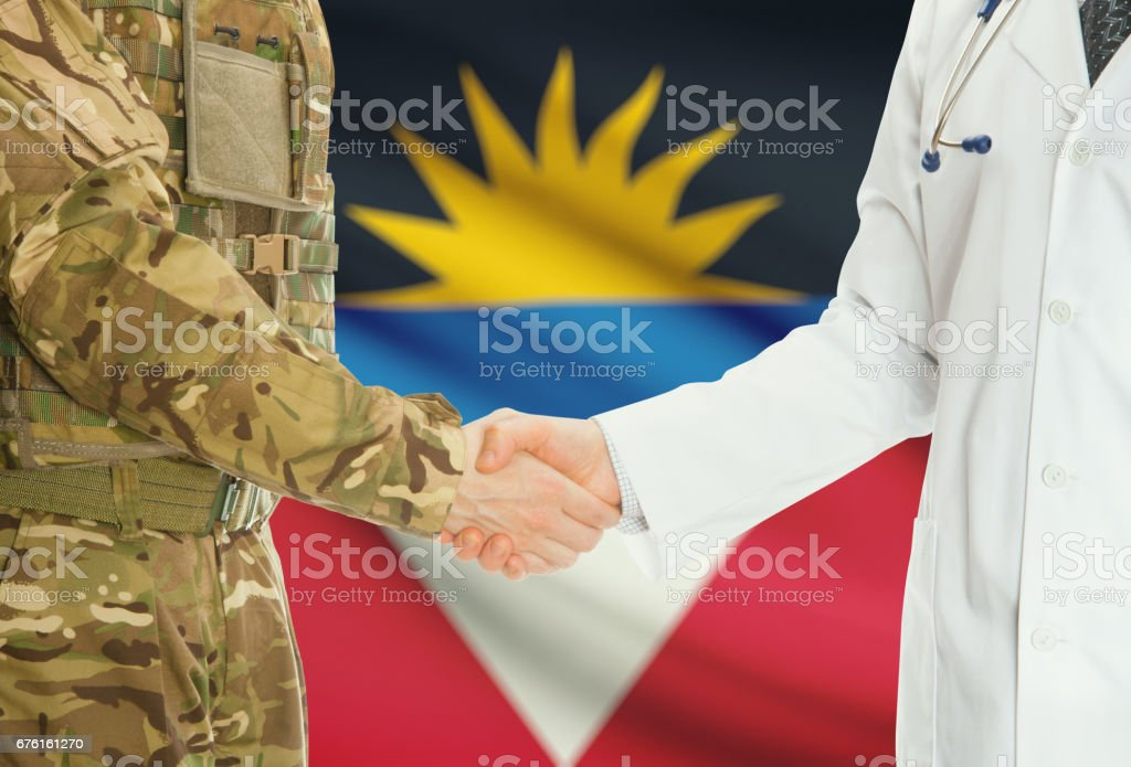Military man in uniform and doctor shaking hands with national flag on background - Antigua and Barbuda stock photo