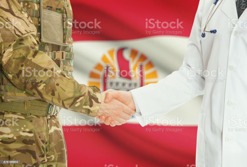 Military man in uniform and doctor shaking hands with national flag on background - French Polynesia stock photo