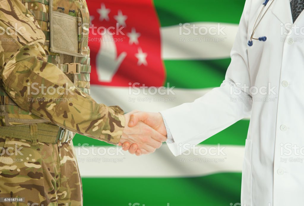 Military man in uniform and doctor shaking hands with national flag on background - Abkhazia stock photo
