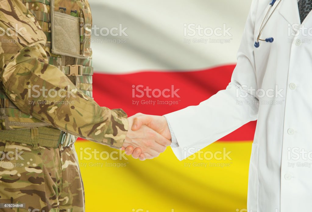 Military man in uniform and doctor shaking hands with national flag on background - South Ossetia stock photo
