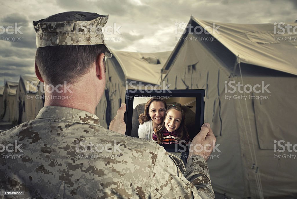 Military man video chats with family on a tablet stock photo