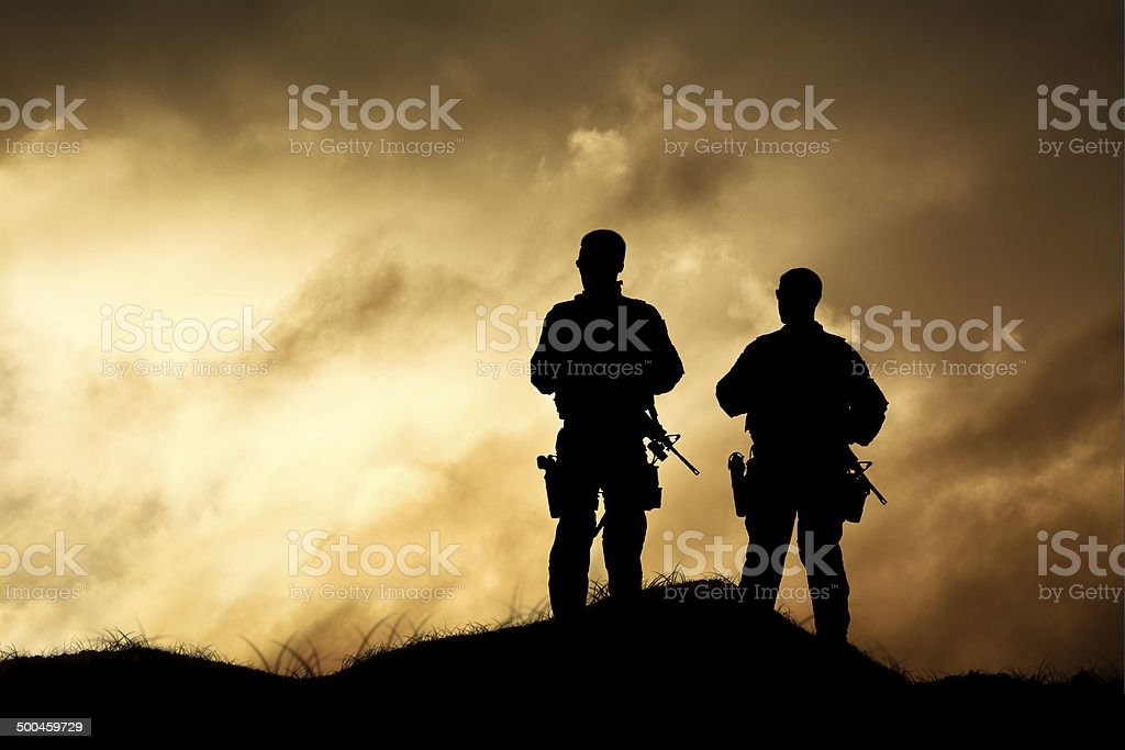 Military Men Over Look a Dramatic Firey Horizon stock photo