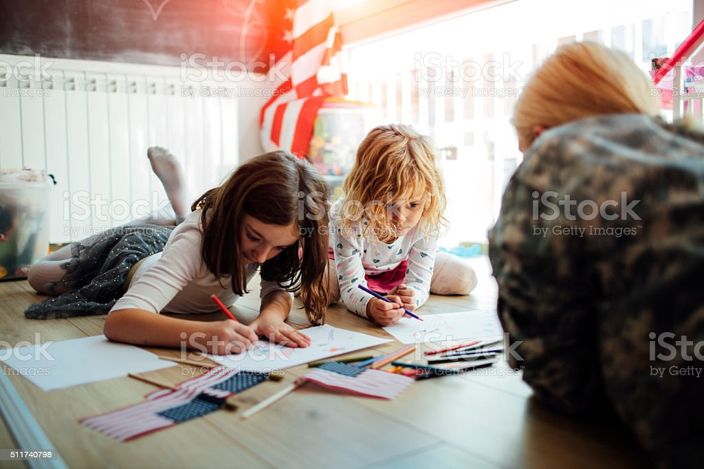 Military Mom Coloring With Her Kids. stock photo