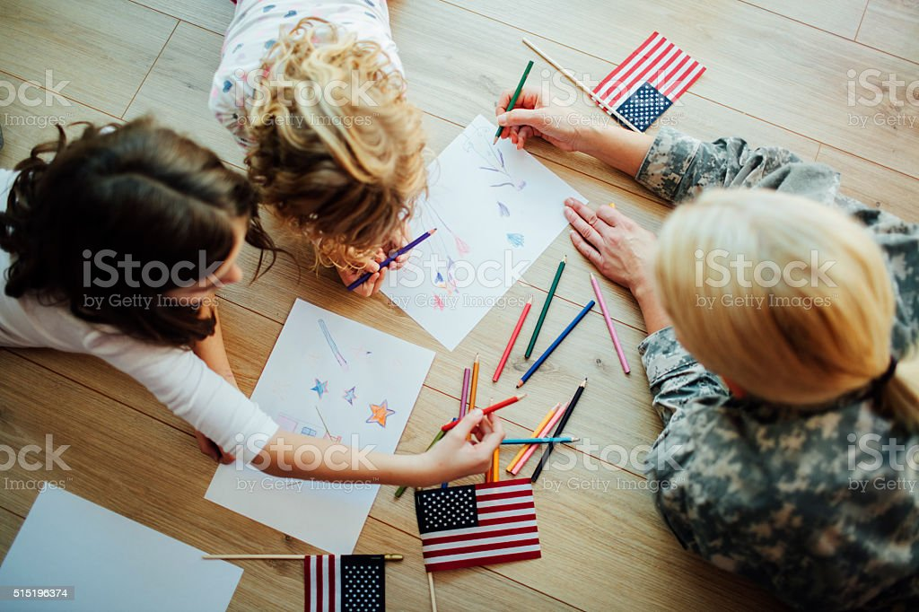Military Mom Coloring With Her Kids, top view. stock photo