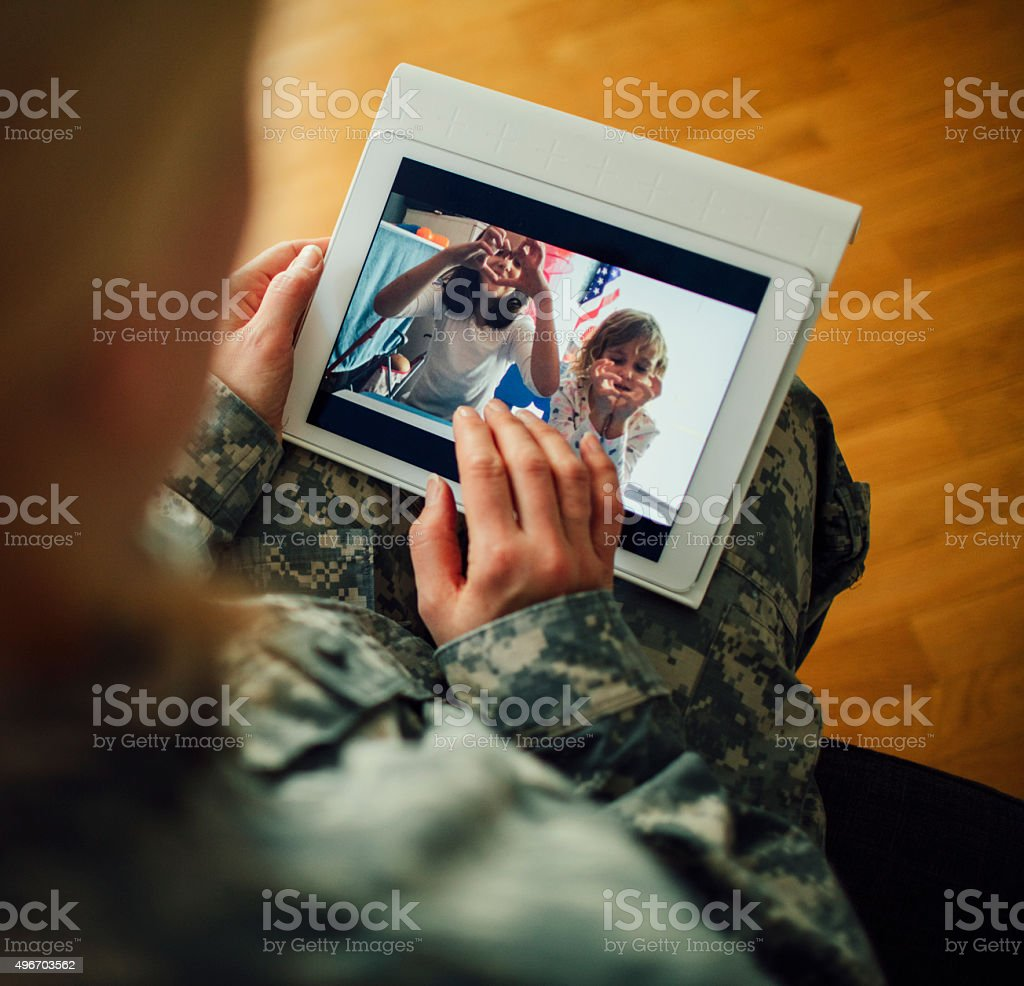 Military Mom Talking With Her Children Over Tablet. stock photo