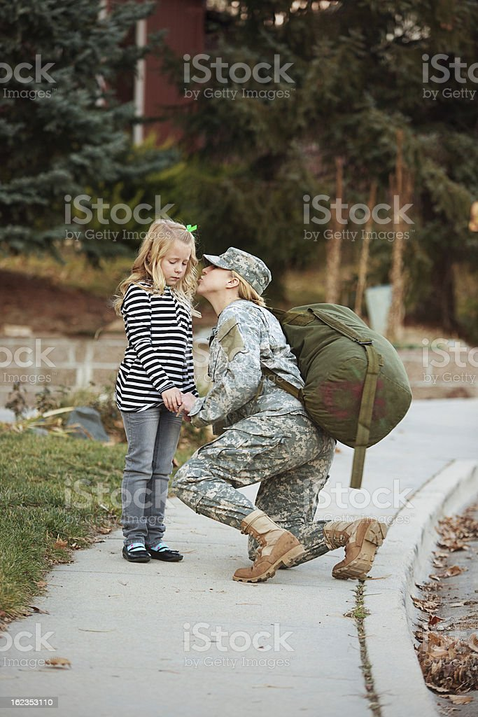Military mother kissing her daughter goodbye royalty-free stock photo