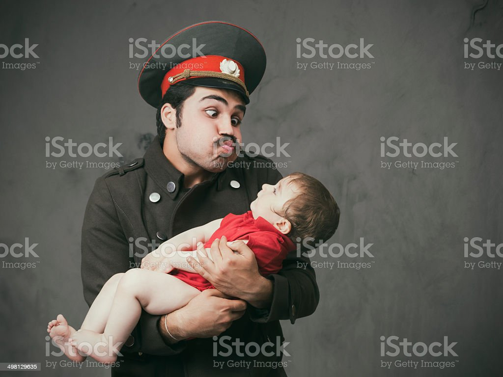 Military officer holding innocent baby royalty-free stock photo