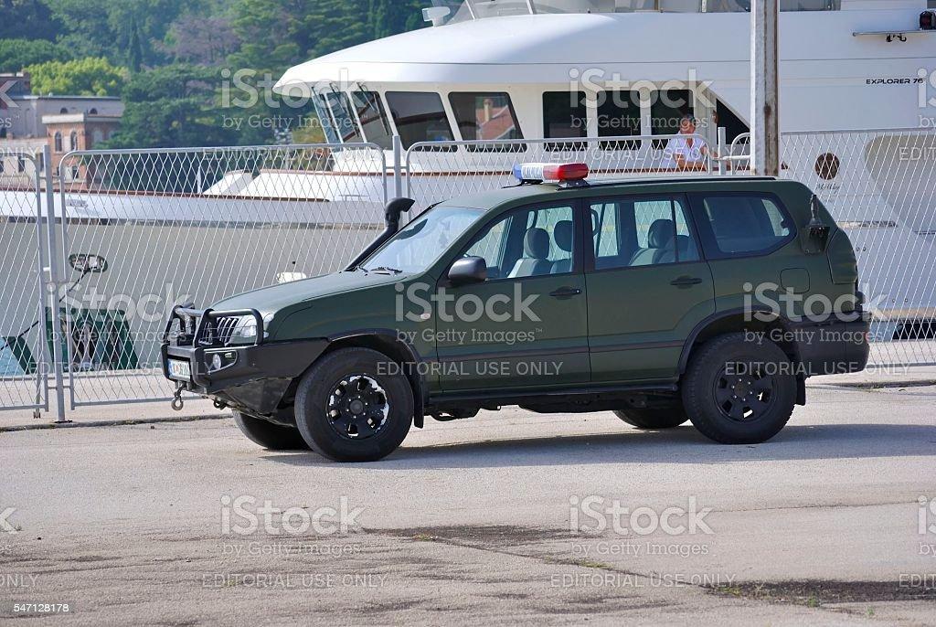 Military police car with boat on the background. zbiór zdjęć royalty-free