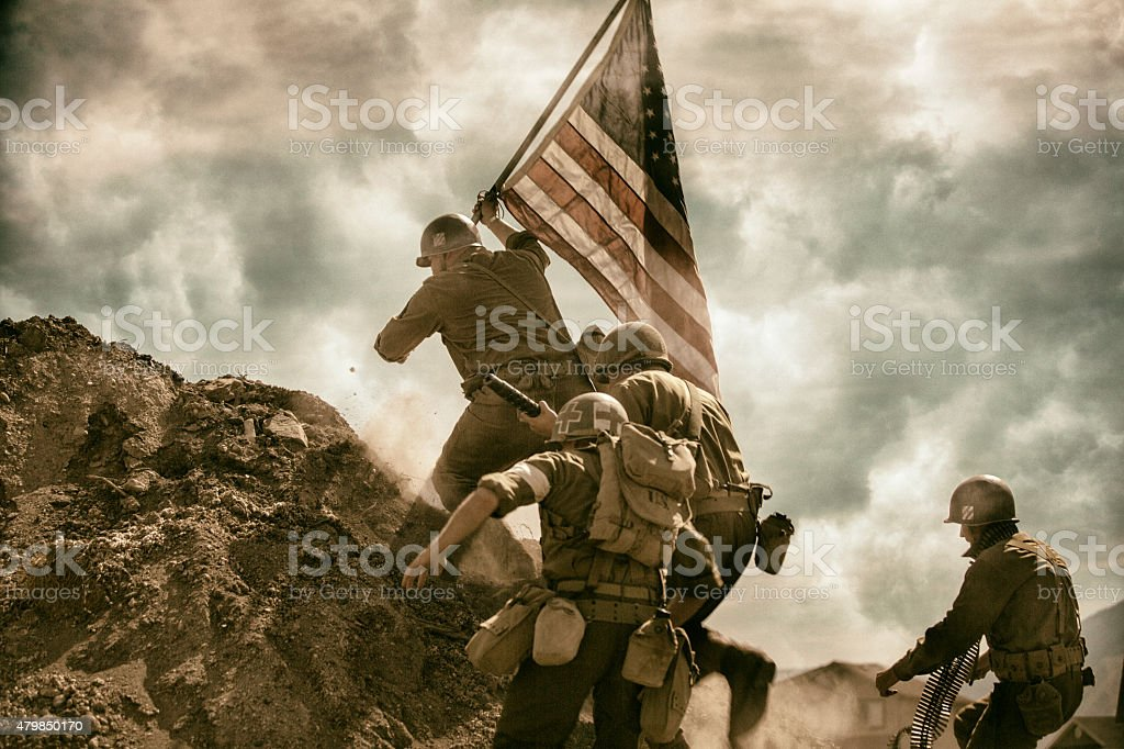 Military running up a hill waving American Flag stock photo