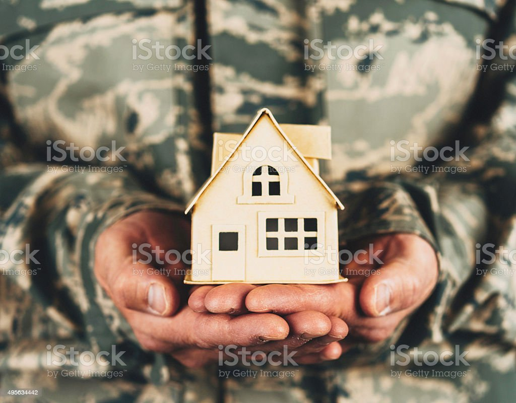 Military service member holding little cardboard house stock photo