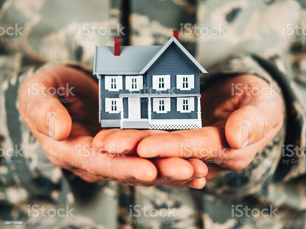 Military service member holding little house. Relocation. stock photo
