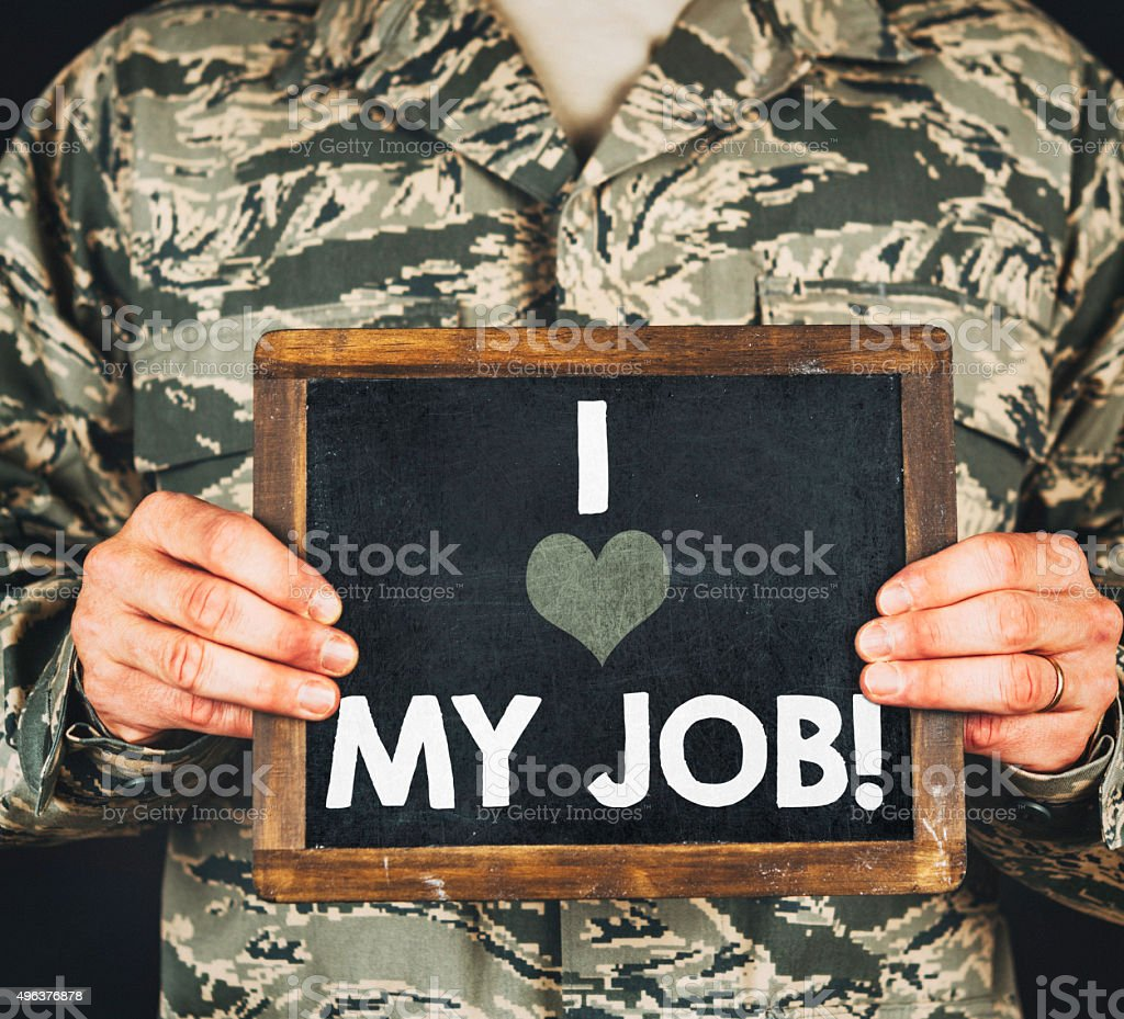 Military service member with I love my job sign stock photo