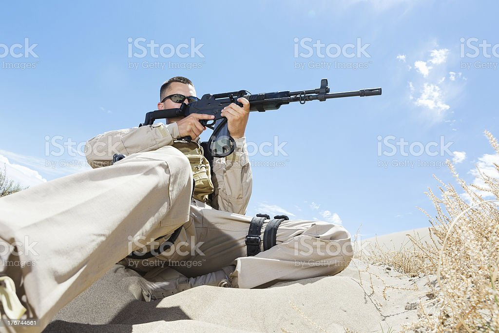 Military sniper using rifle in desert training exercise royalty-free stock photo
