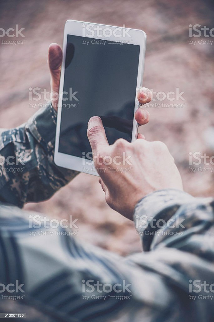 US military soldier using digital tablet in the field stock photo