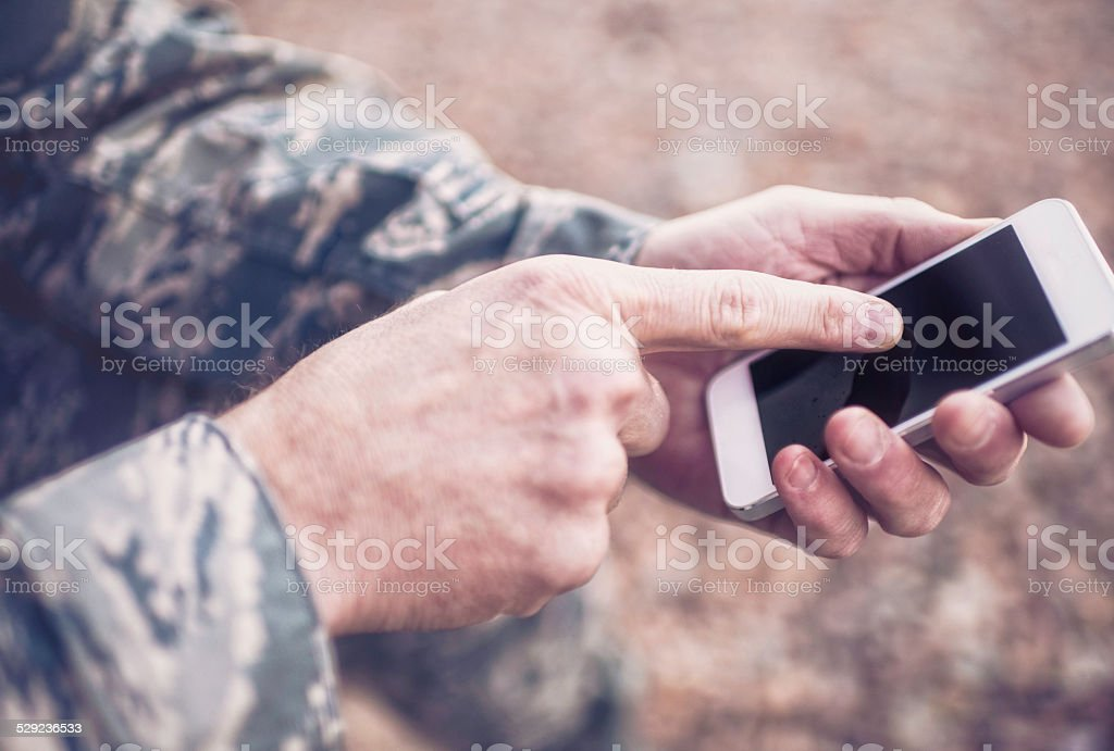 US military soldier using digital technology in the field stock photo
