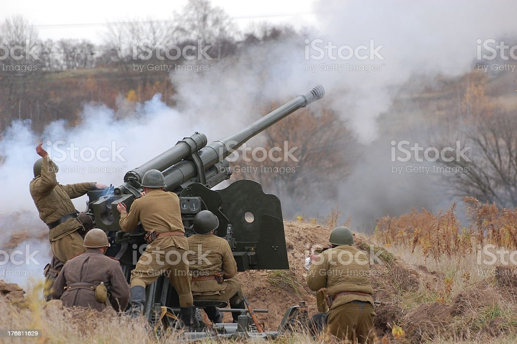 Military soldiers firing an artillery canon stock photo