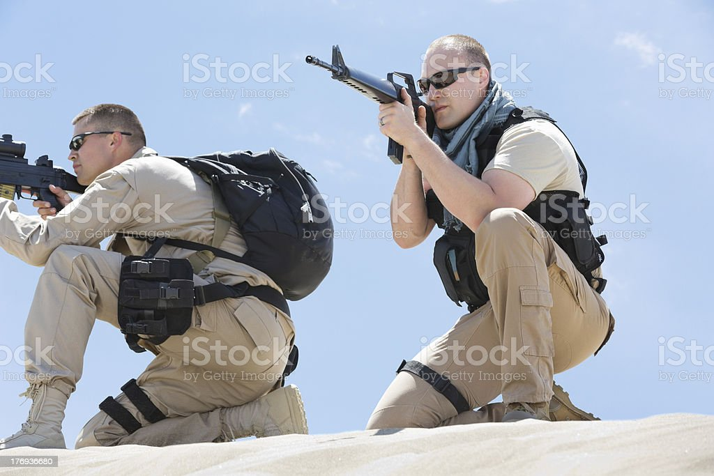 Military soldiers using weapons during desert combat royalty-free stock photo
