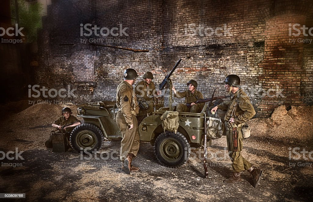 WWII US Military Squadron Discussing Military Operation In Abandoned Building stock photo