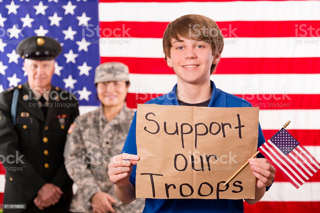 Military:  Teenage boy shows appreciation to veterans. USA flag. stock photo