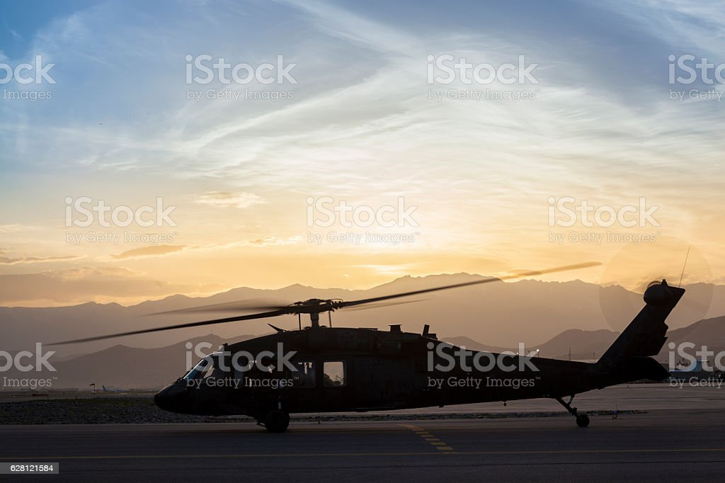 Military utility helicopter on the taxiway at sunset. stock photo