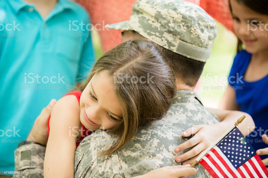 U.S. military veteran welcomed home by family. Children, hugs. stock photo