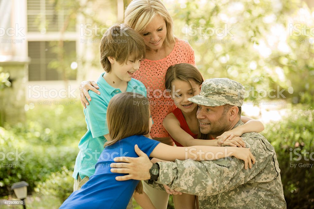 U.S. military veteran welcomed home by family. Mom, children. Home. stock photo