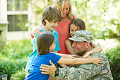 U.S. military veteran welcomed home by family. Mom, children. Home.