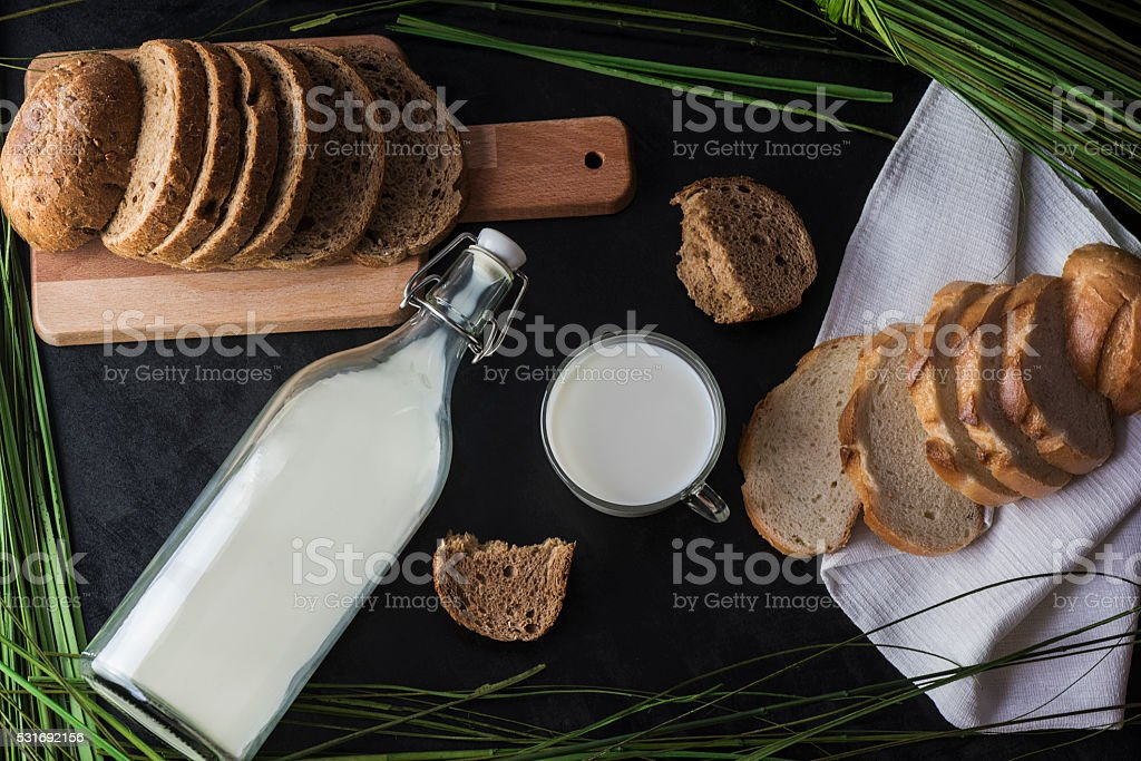 Milk and bread, laid out on a dark background stock photo