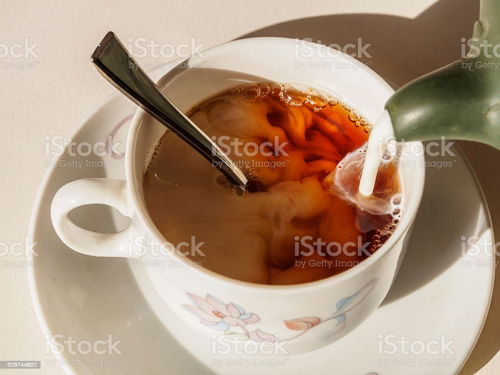 Milk being poured into tea cup on table stock photo