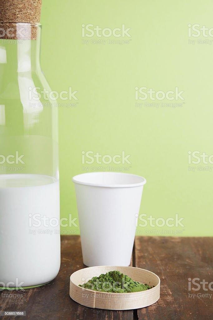 milk bottle, matcha, paper glass on green back stock photo