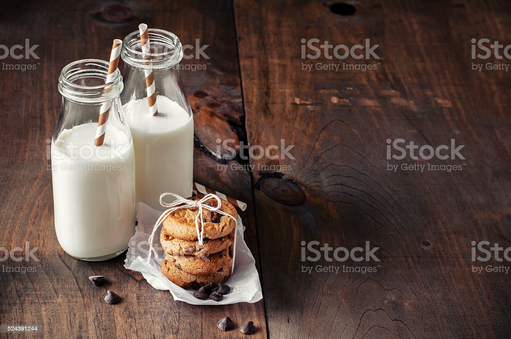 Milk bottles and chocolate chips cookies. stock photo