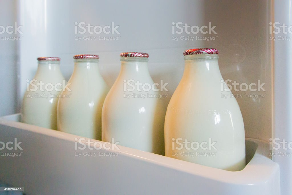 Milk Bottles in Fridge Door stock photo