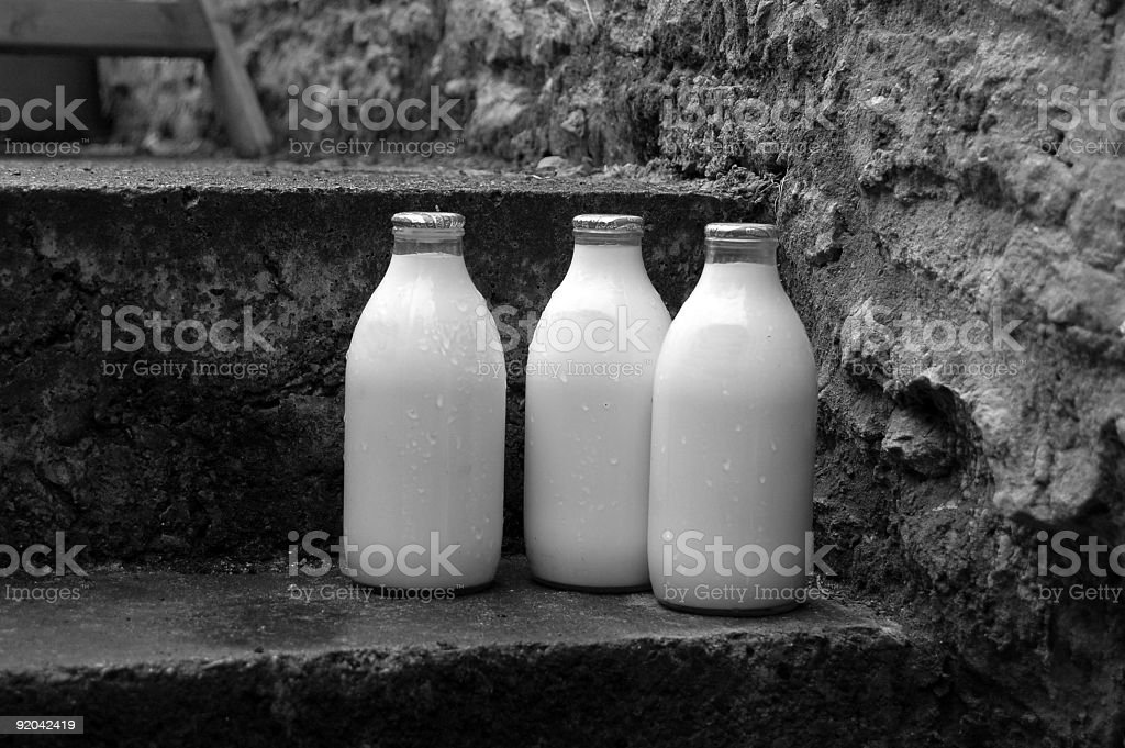 Milk bottles on a step in the rain royalty-free stock photo