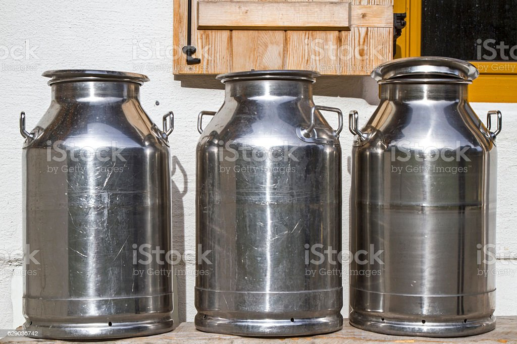Milk cans in front of the mountain hut stock photo