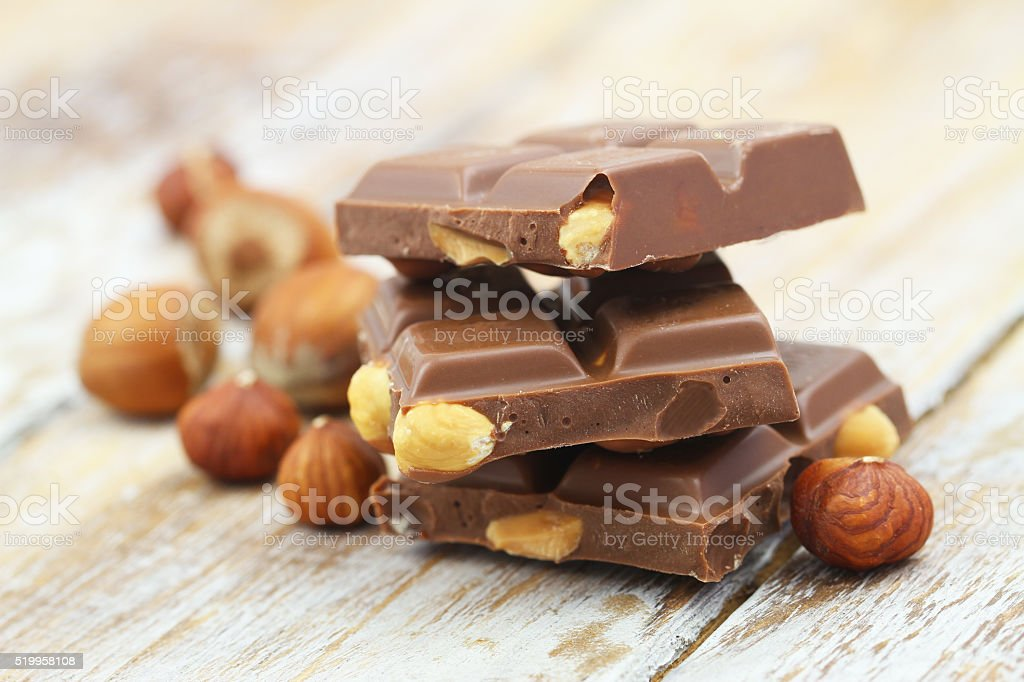 Milk chocolate pieces with whole hazelnuts on rustic wooden surface stock photo