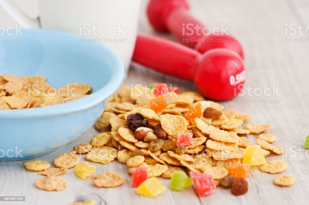 Milk, corn flakes, candied fruits and dumbbells stock photo