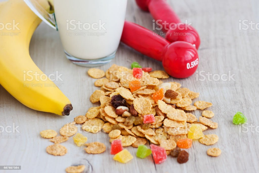 Milk, corn flakes, candied fruits, banana and dumbbells stock photo