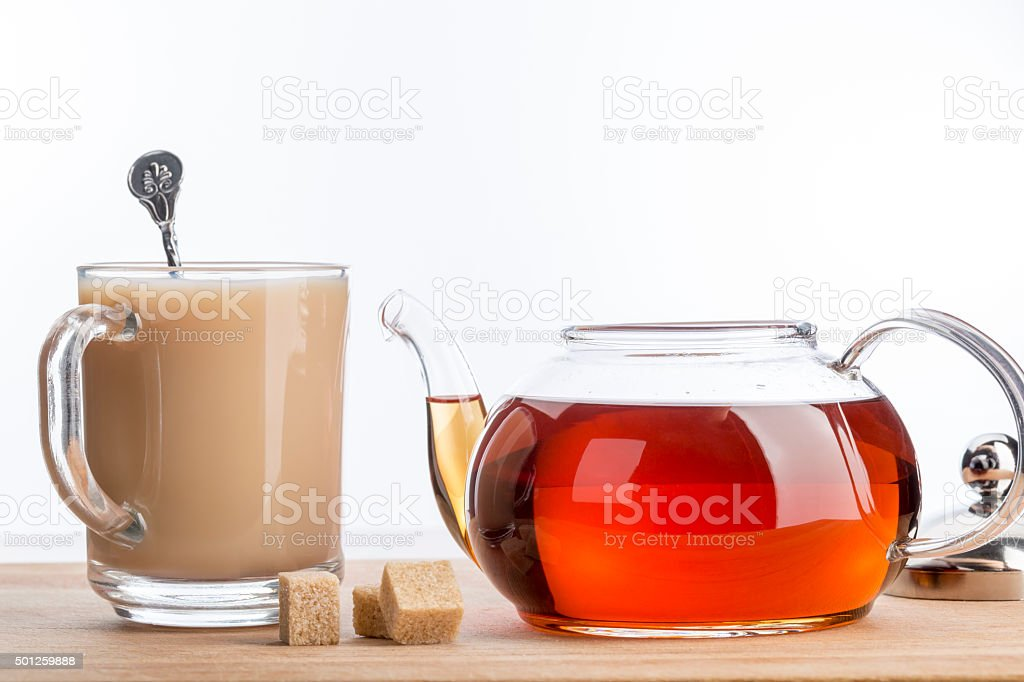 Milk dissolves in glass cup of hot tea with spoon stock photo