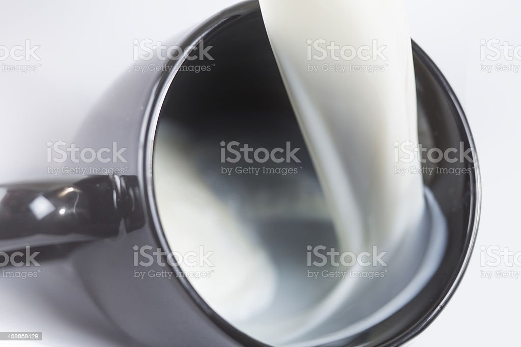 Milk flowing into a mug stock photo