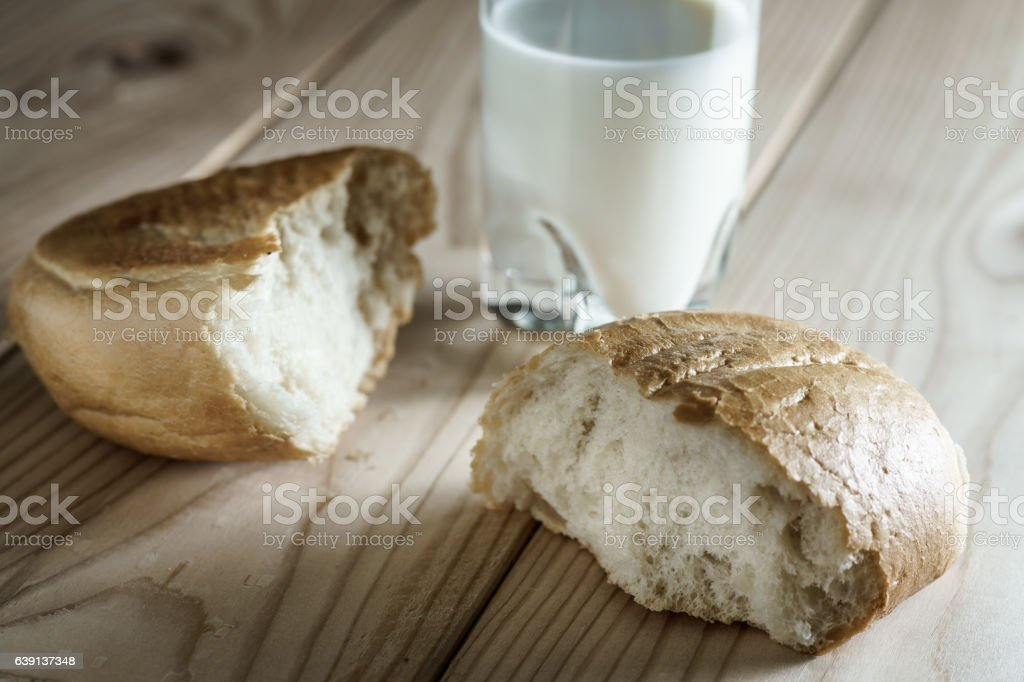 Milk in a glass. Bread on wooden background. Bio products stock photo