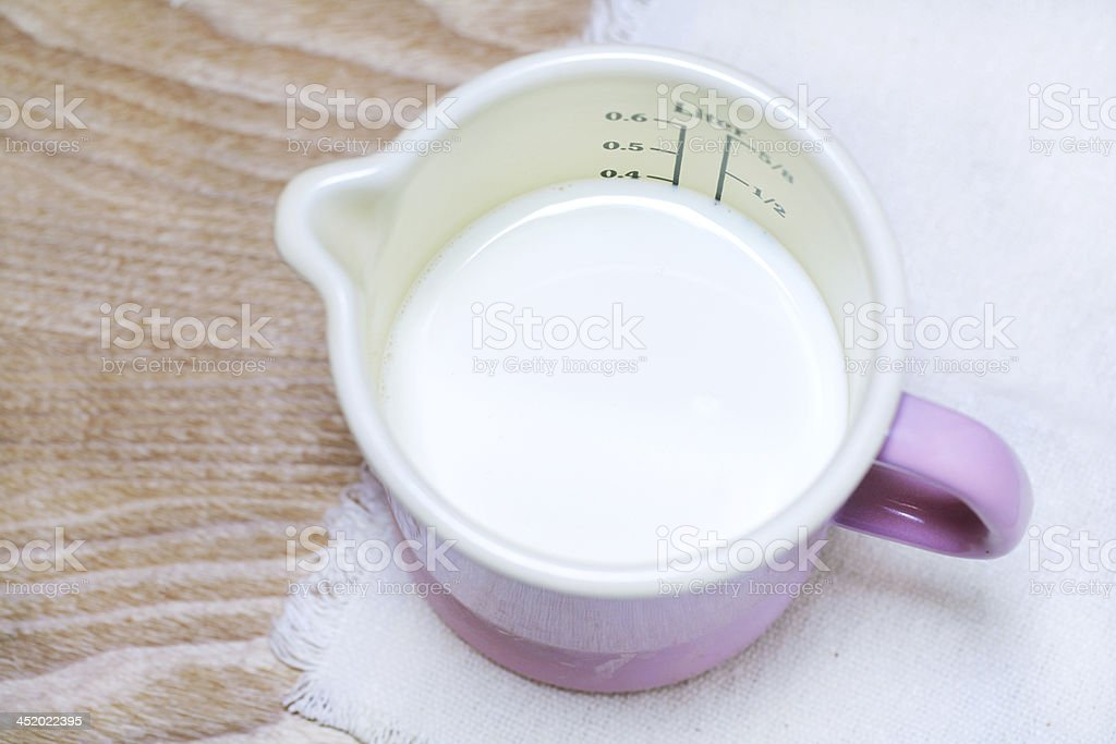 Milk in a measuring enamel cup of pink color stock photo