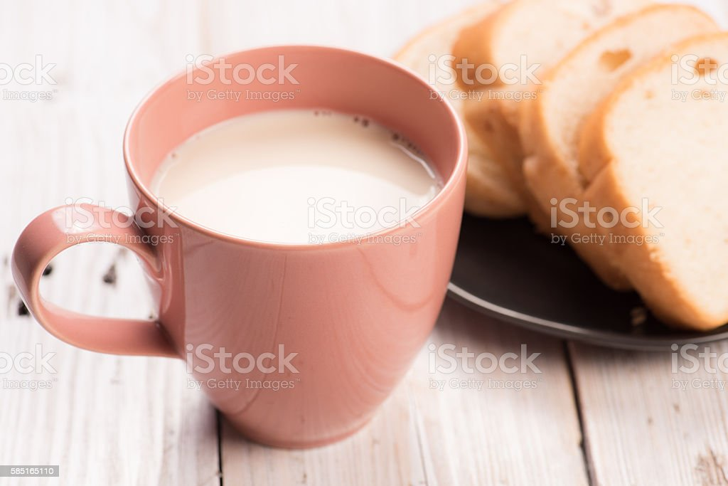 milk in a pink cup with fresh buns. stock photo