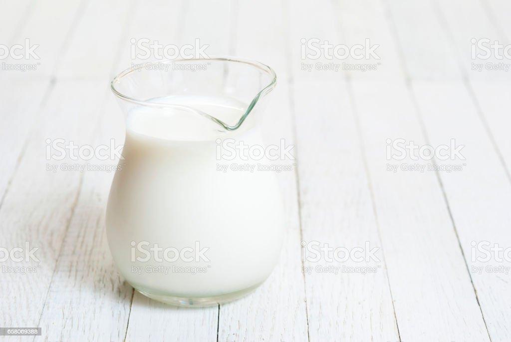 Milk jug on white wood stock photo