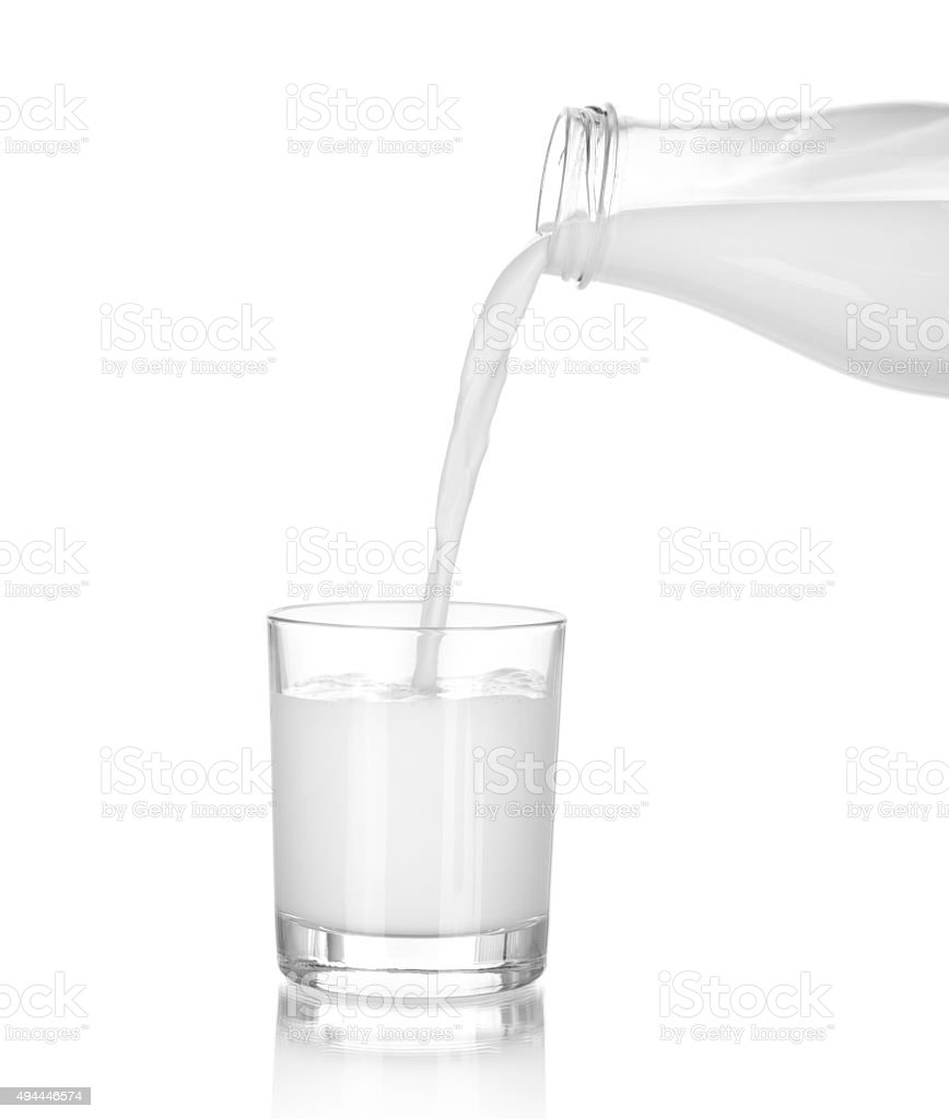 Milk pouring from a bottle in a glass stock photo